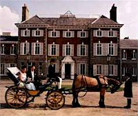 A couple sitting in a carriage outside York House